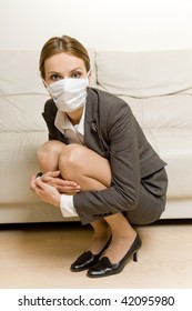 young woman wearing protective mask crouching fearful