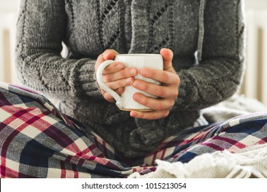 Young woman wearing pyjamas and cozy woolly gray cardigan holding mug of tea on bed