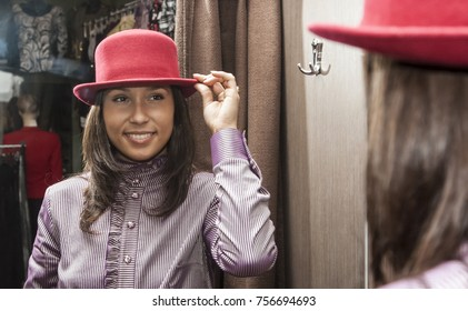Young woman wearing  a red hat in a fitting room of a clothes store  (main focus in the mirror).