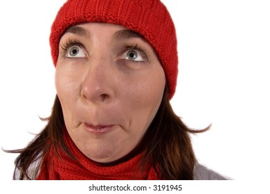 A young woman wearing a red knit cap and scarf looks up with eyes wide open in amazement and incredulity!