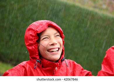 Young woman wearing a red raincoat enjoying the rain and having fun outside.