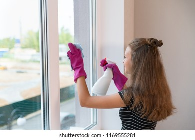 Young woman wearing rubber gloves cleaning the glass on a window with a detergent spray and cloth with copy space