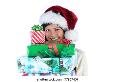Young woman wearing a Santa Claus hat holding a large stack of assorted Christmas presents. Horizontal format isolated on white.