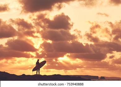 Young woman wearing shorty wetsuit, standing on beach with surfboard in her hands and enjoying stunning sunset after evening surfing session - water sports concept. Baleal, Peniche, Portugal