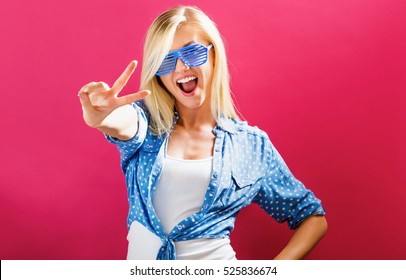 Young woman wearing shutter shades sunglasses on a pink background
