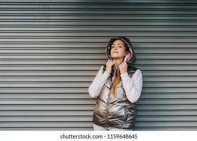 Young woman wearing silver down vest, posing ootdoors