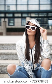 Young woman wearing silver jacket and sunglasses