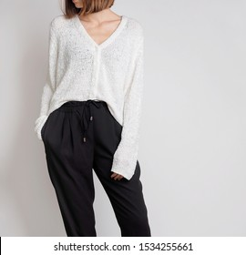 Young woman wearing simple stylish outfit with white sweater and black trousers isolated on light grey background. Copy space