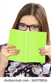 the young woman wearing spectacles holds the book in hand