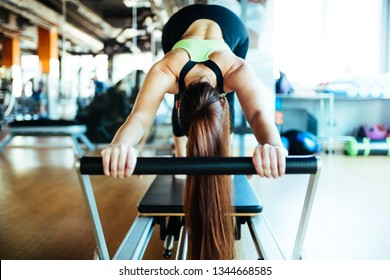 Young woman wearing sports clothing doing reformer exercises on pilates machine indoors in a studio