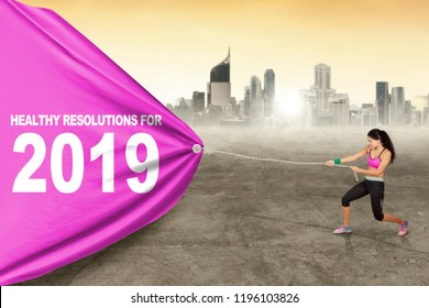 Young woman wearing sportswear while pulling banner with text of healthy resolutions for 2019. Shot with city background