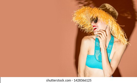 Young woman wearing straw hat with fringe and swimsuit having fun over bright background, shorts, sunglasses, sunbathing, summer vacation, happiness, fun, enjoying, sunny