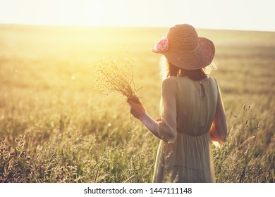 young woman wearing straw hat and yellow silk dress enjoying nature, holding bouquet of wildflowers, copy space