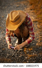 Young woman wearing straw hat, red plaid shirt, and cowgirl boots using a pocket point and shoot camera to capture a detail on the farm.