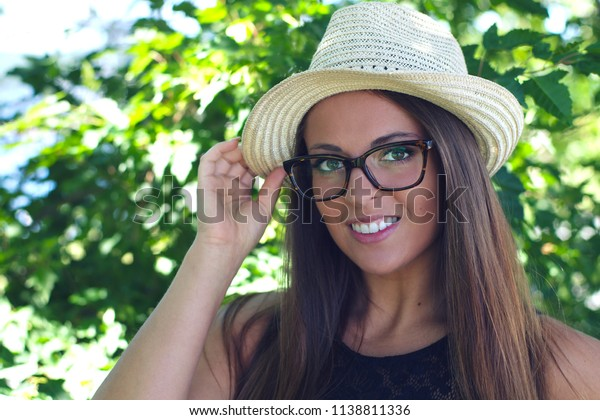 young woman wearing straw hat and eye glasses summer smiling portrait