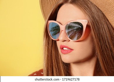 Young woman wearing stylish sunglasses with reflection of palm trees and hat on yellow background
