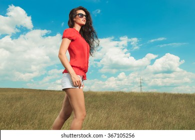young woman wearing sunglasses and red blouse walking in the fields with hands in pockets