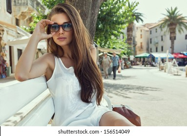 Young woman wearing sunglasses and resting on bench