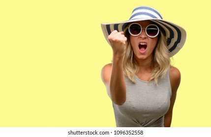 Young woman wearing sunglasses and summer hat irritated and angry expressing negative emotion, annoyed with someone