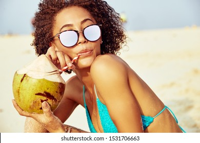 Young woman wearing sunglassses and a bikini drinking from a coconut while relaxing on a tropical beach