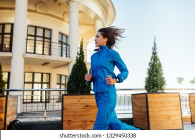 Young woman wearing sweat suit jogging on empty city street in the morning