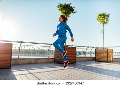 Young woman wearing sweat suit warming up before training session