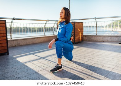 Young woman wearing sweat suit stretching before jogging exercise