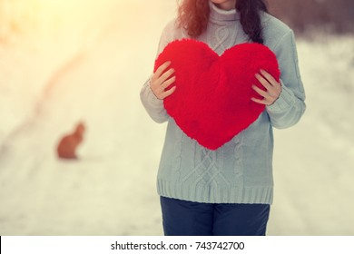 Young woman wearing sweaters holding red heart outdoors in winter