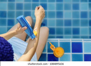 Young woman wearing swimsuit applying sunscreen lotion at swimming pool, Summer vacation concept