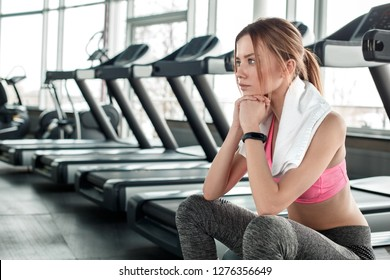 Young woman wearing towel around neck in gym healthy lifestyle sitting on treadmill leaning on fists looking in front thoughtful