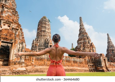 Young woman wearing traditional dress in front of traditional Temple in Ayutthaya, Thailand. View from behind.