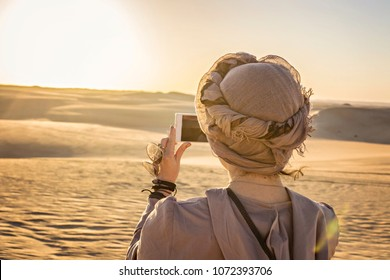 Young woman wearing turban (back view) taking picture of sunset in desert, Siwa, Egypt