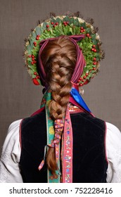 The young woman is wearing a Ukrainian traditional garment of wedding. She is photographed from back.