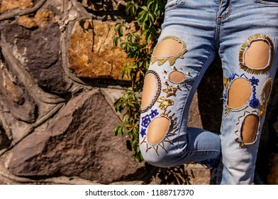 Young woman wearing unsual jeans leaning towards stones wall, street fashion
