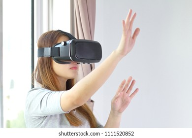 Young woman wearing virtual reality glasses at home. A virtual reality headset is a head-mounted device that provides virtual reality for the wearer.