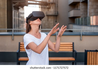 Young woman wearing virtual reality goggles headset, vr box outdoors. Connection, technology, new generation, progress concept. Girl trying to touch objects in virtual reality