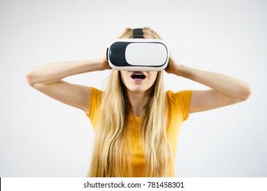 Young woman wearing virtual reality goggles headset, vr box. Studio shot on gray