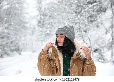 Young woman wearing warm clothes outdoors on snowy day. Winter vacation