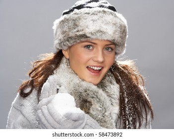 Young Woman Wearing Warm Winter Clothes And Fur Hat Holding Snowball In Studio