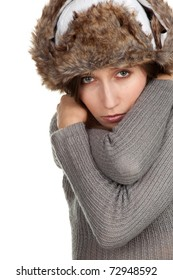 young woman wearing a warm winter hat and grey sweater, black background