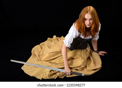 young woman wearing in white blouse, gold long skirt and black corset sitting with longsword