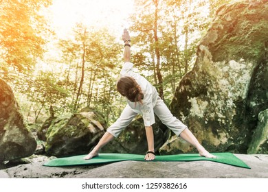 Young woman wearing in white clothing exercising on yoga mat in forest, healthy lifestyle outdoor.