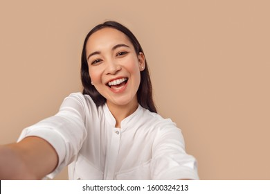 Young woman wearing white shirt with dark long hair standing isolated on bage background taking selfie photo on smartphone looking camera laughing happy close-up