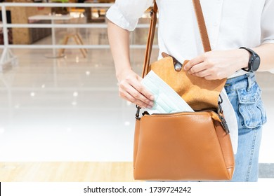 Young woman wearing white shirt and jeans with  medical mask in hand and put it in shoulder bag. The concept of new normal of healthcare and protection during coronavirus pneumonia outbreak.