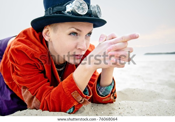 Young woman wearing wintage hat and danger style glasses pointing fingers like using a gun