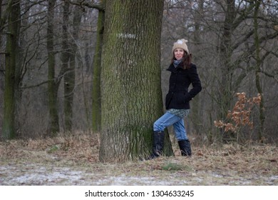 young woman wearing winter clothes is standing next to tree in the forest in winter