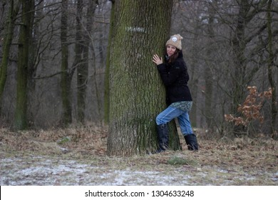 young woman wearing winter clothes is standing next to tree an hug the tree in the forest in winter