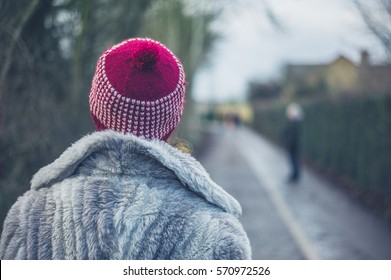 A young woman wearing winter coat and hat is standing outside in the park 011a7010ee6