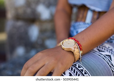 young woman wearing a wooden watch