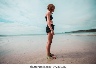 A young woman wearing workout clothing is standing on the beach about to go running